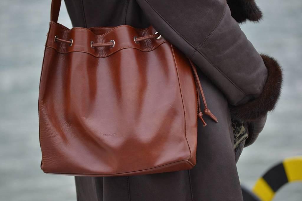 Bolso de cuero color coñac y abrigo de cuero marrón